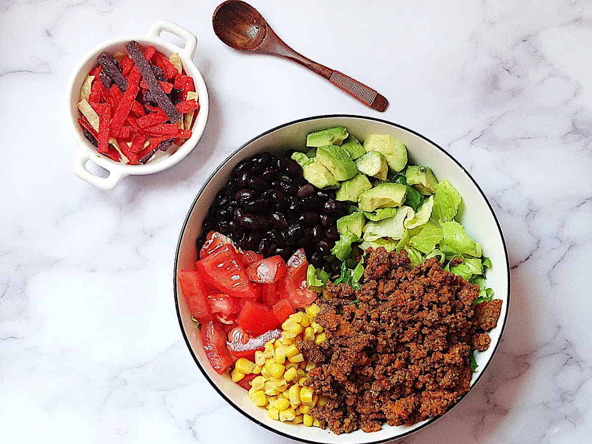 Taco salad ingredients in a large bowl