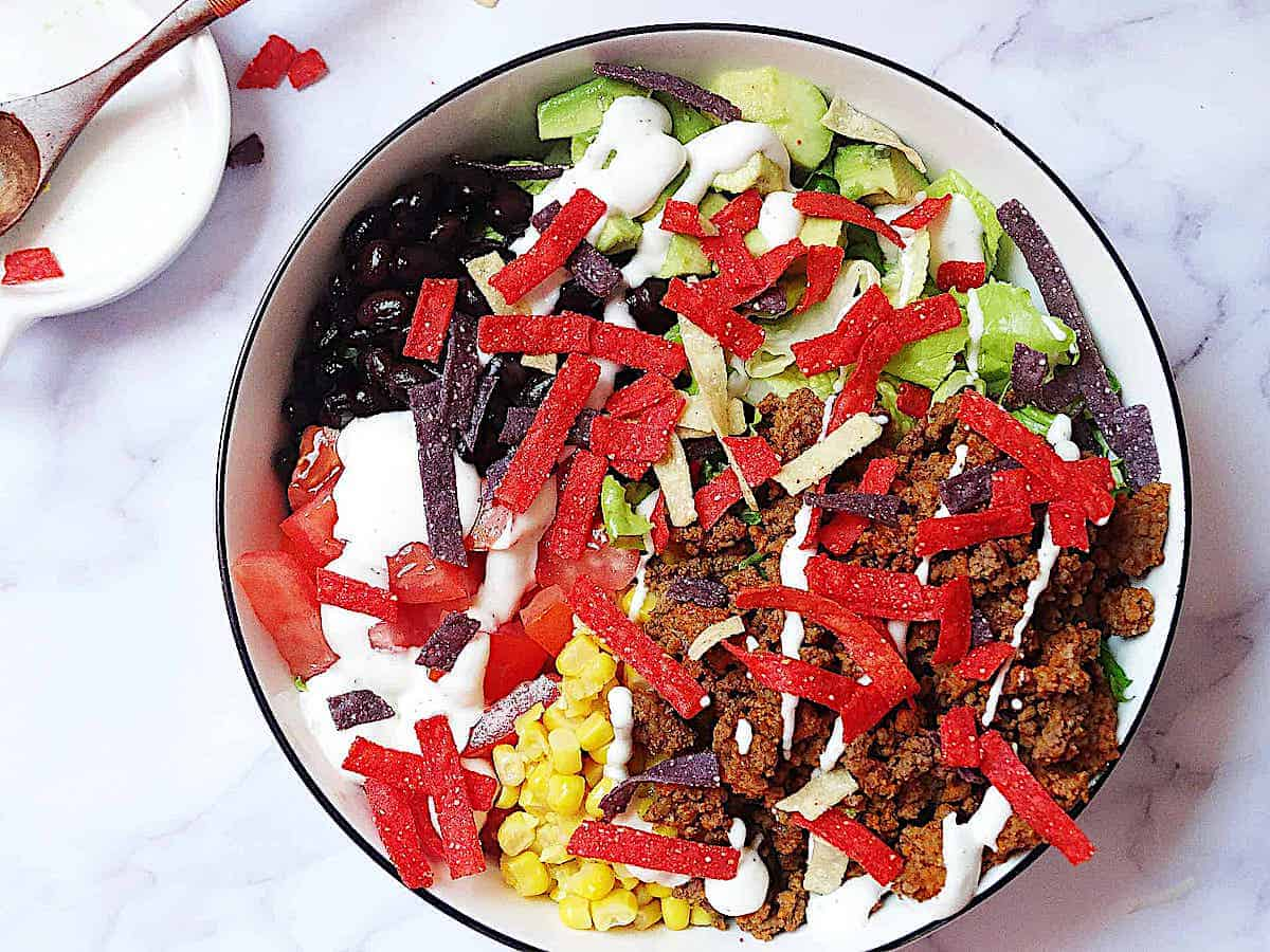 healthy taco salad with beef, avocado and topped with ranch dressing