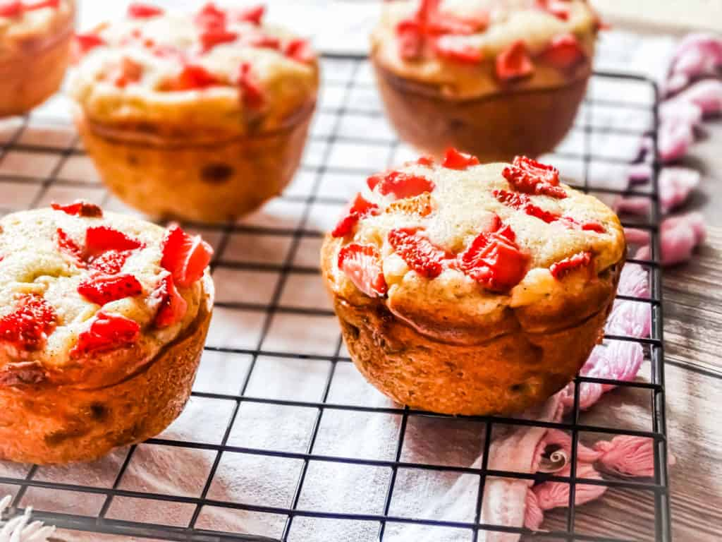 the best banana strawberry muffins on a wire rack topped with strawberries