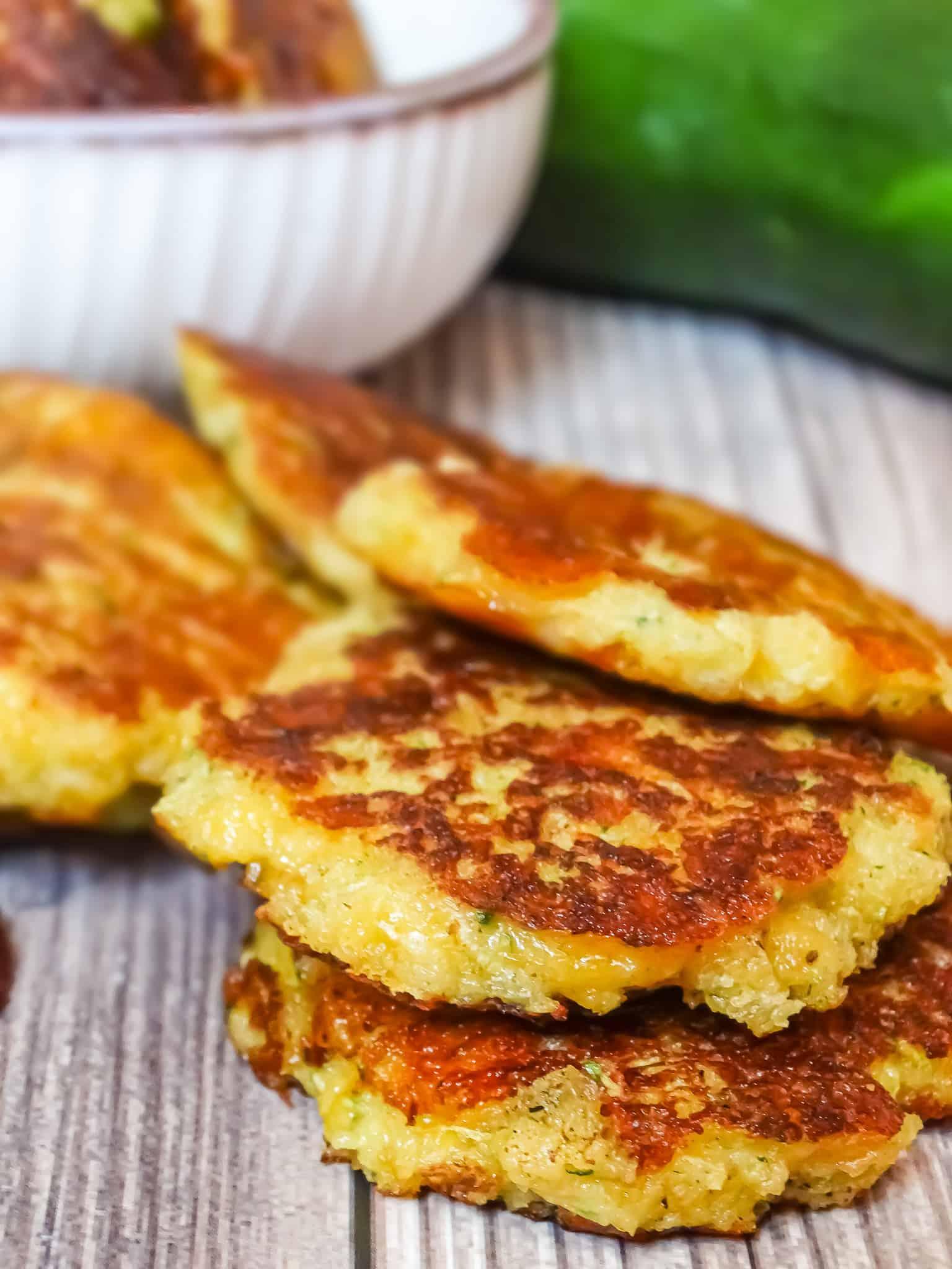 zucchini fritter recipe: cheesy zucchini fritters on a wooden backdrop