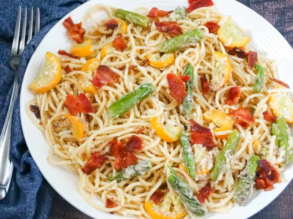 double vegetable pasta with parmesan sauce in a white plate