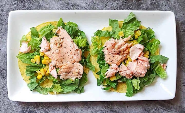 tostada layered with romaine, corn, and salmon