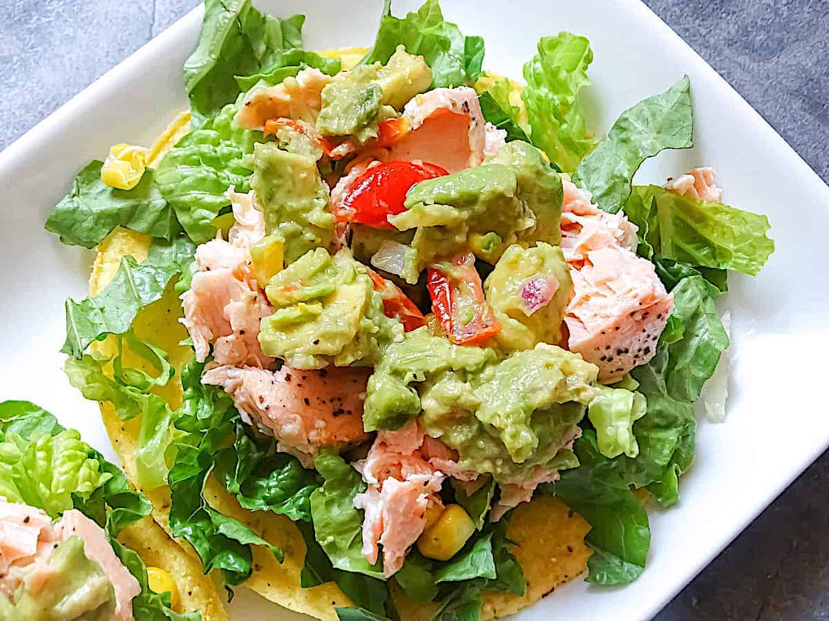 close up of 1 tostada with salmon, romaine, lettuce, corn, and tomato salsa