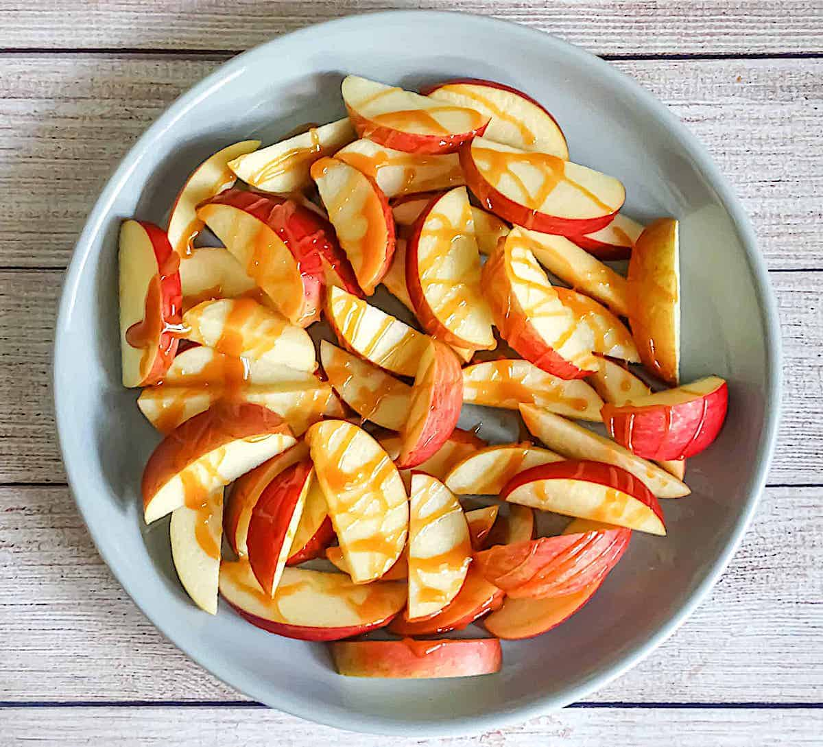 sliced apples topped with caramel on a grey plate