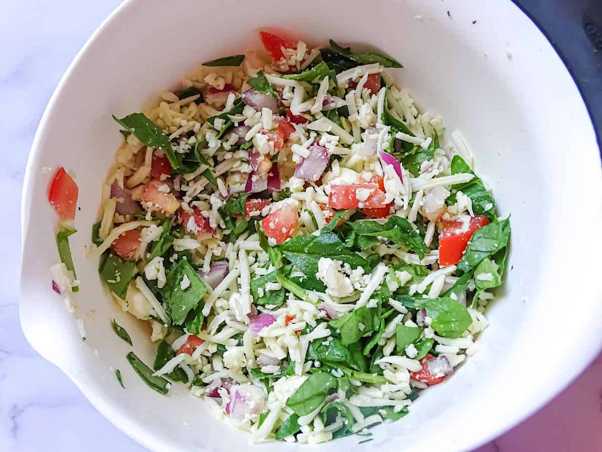 spinach, onion, cheese, and tomato chopped in a mixing bowl