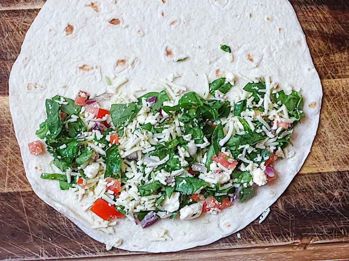 a tortilla shell filled partly with fresh spinach, cheese, tomato and onion