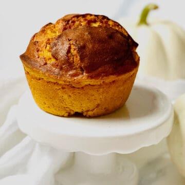 pumpkin cream cheese muffin on a white pedestal