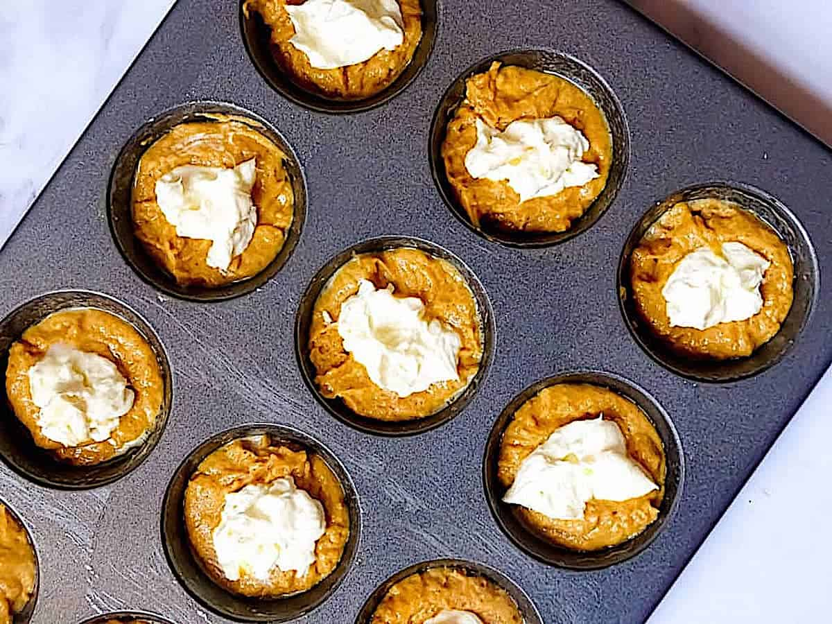 pumpkin muffin batter topped with cream cheese in a muffin tin