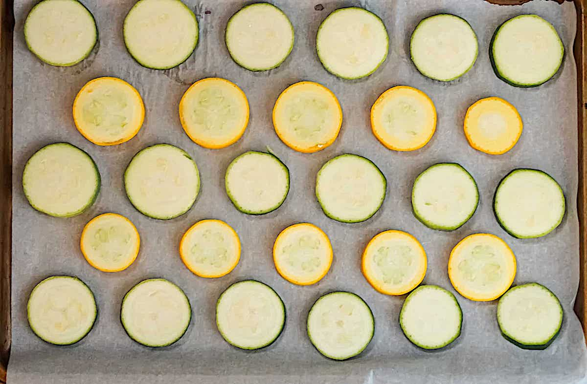sliced yellow and green squash on a baking sheet