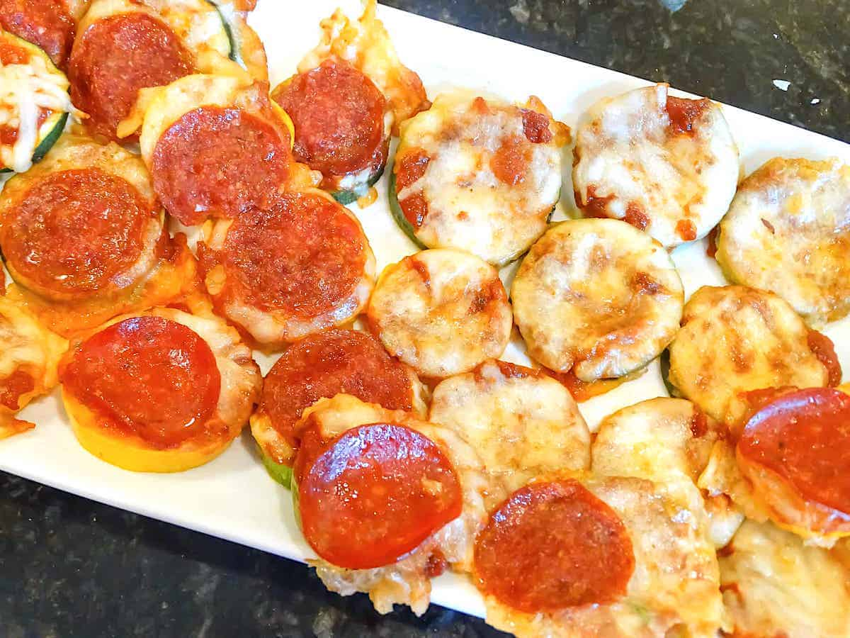 zucchini pizza bites, half with pepperoni and half without on a white plate