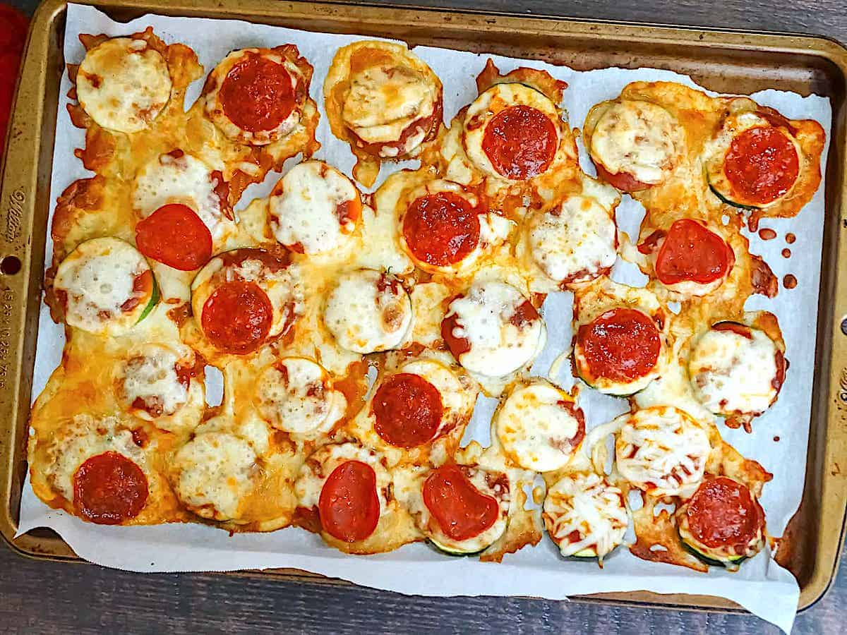 zucchini slices baked with mozzarella and pepperoni on a baking sheet