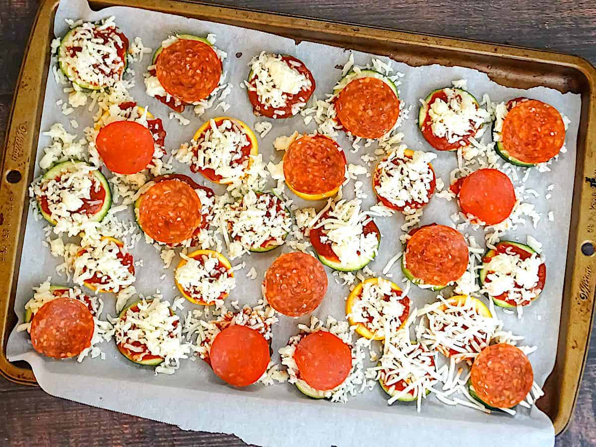 zucchini slices topped with mozzarella and pepperoni on a baking sheet