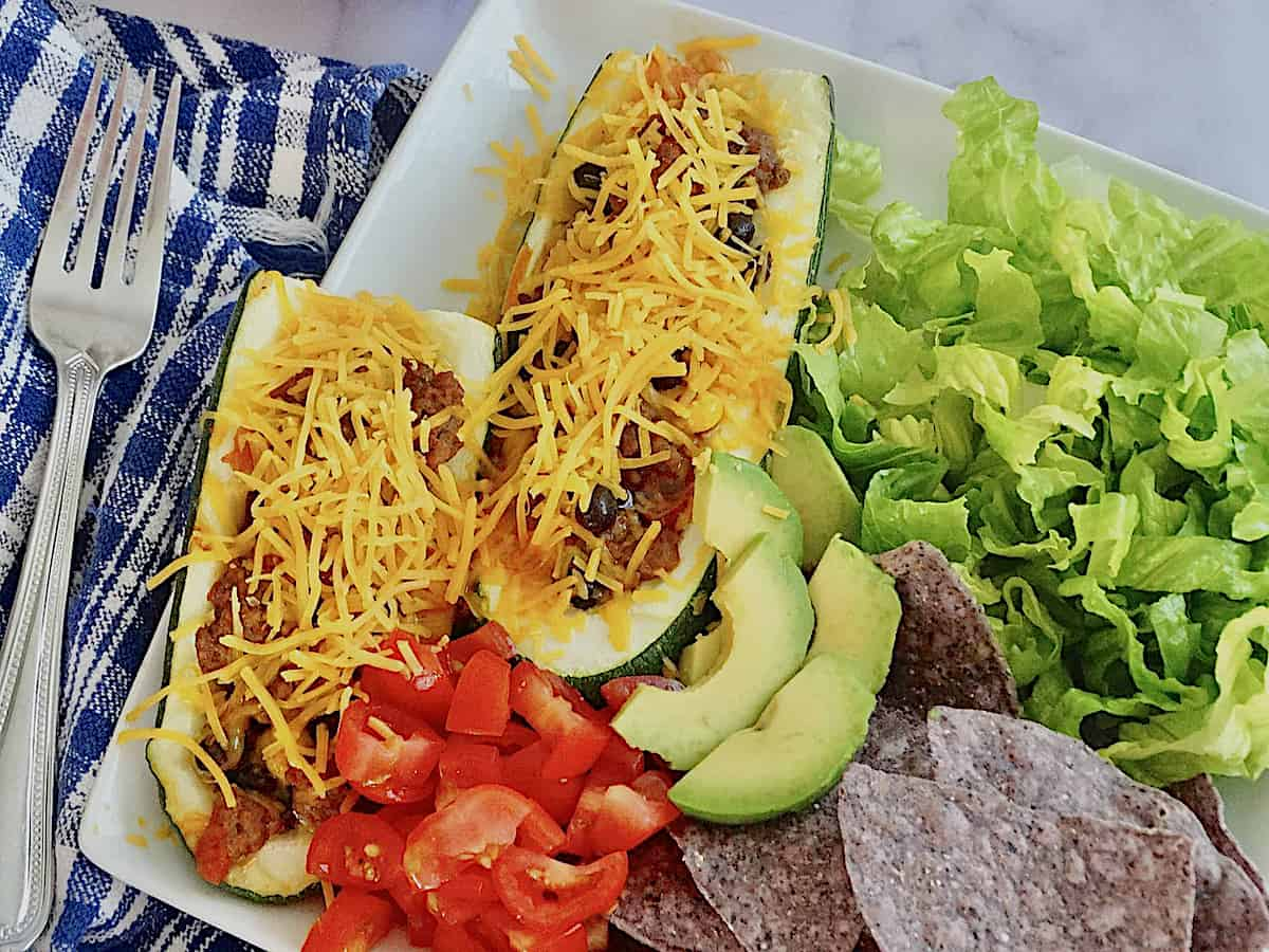 zucchini taco boats on a plate with tomatoes, avocados, and lettuce