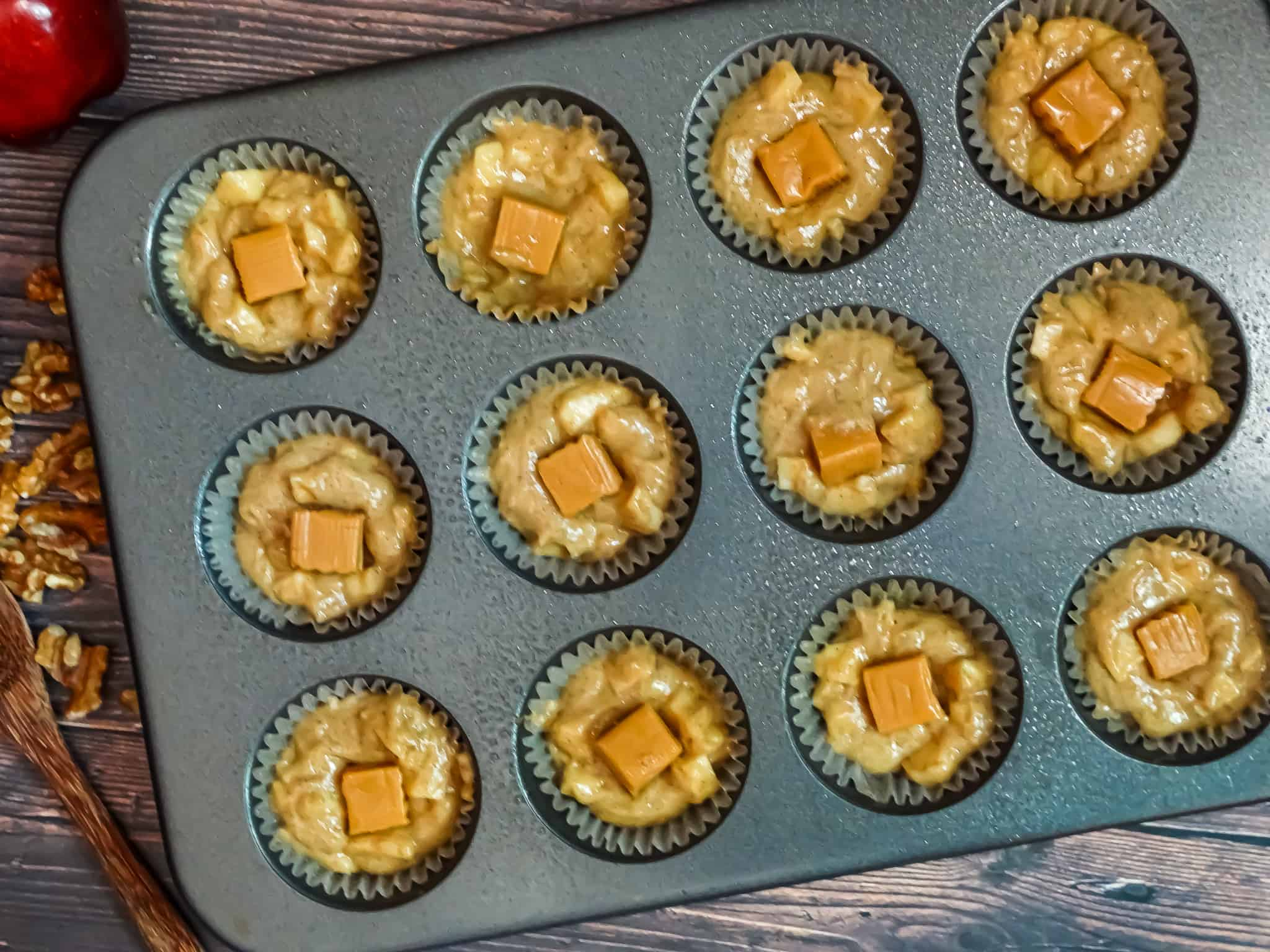 muffin batter in a tin with caramel on top
