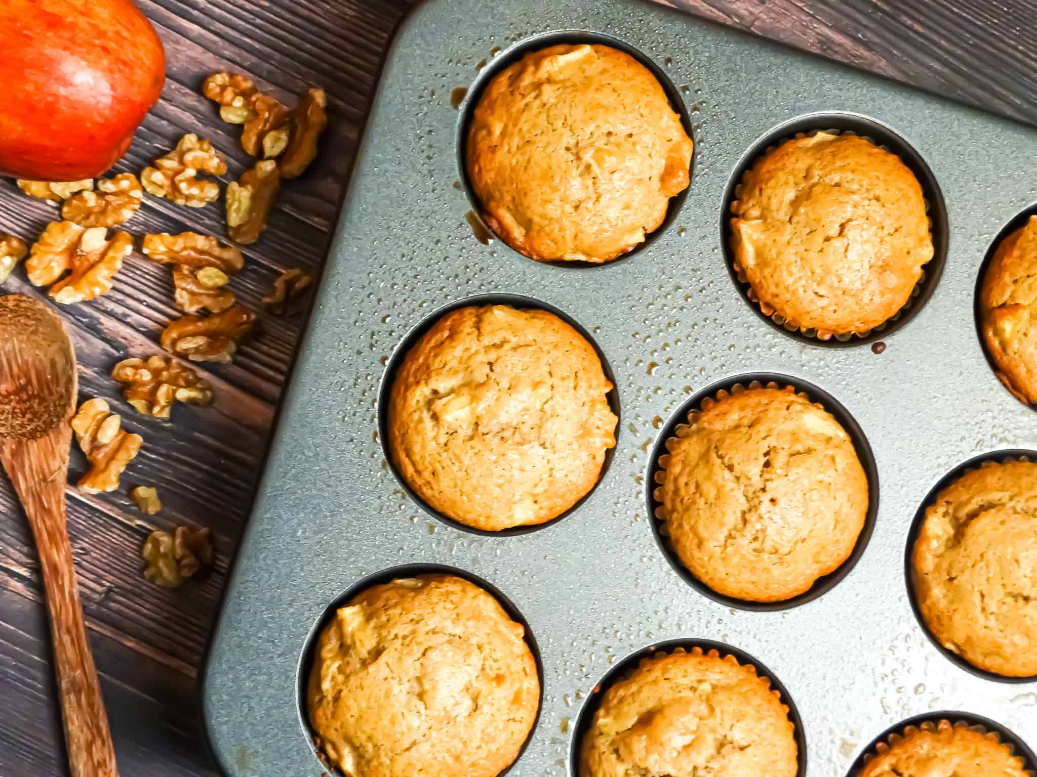 baked caramel apple muffins in a muffin tin