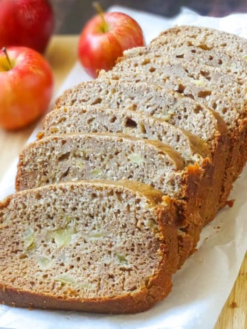 bread machine apple bread on a cutting board surrounded by apples