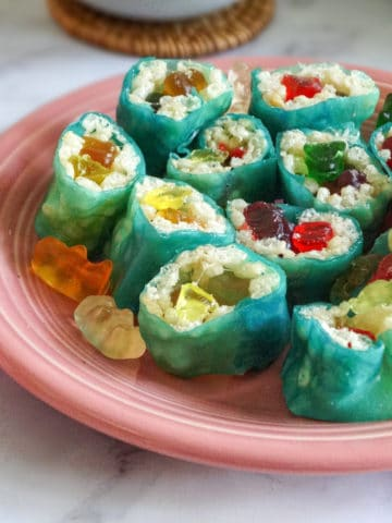 rice Krispy treat sushi on a pink plate and white background