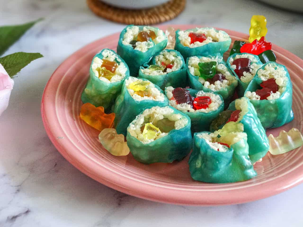 candy sushi cut into slices on a pink plate surrounded by extra gummy bears