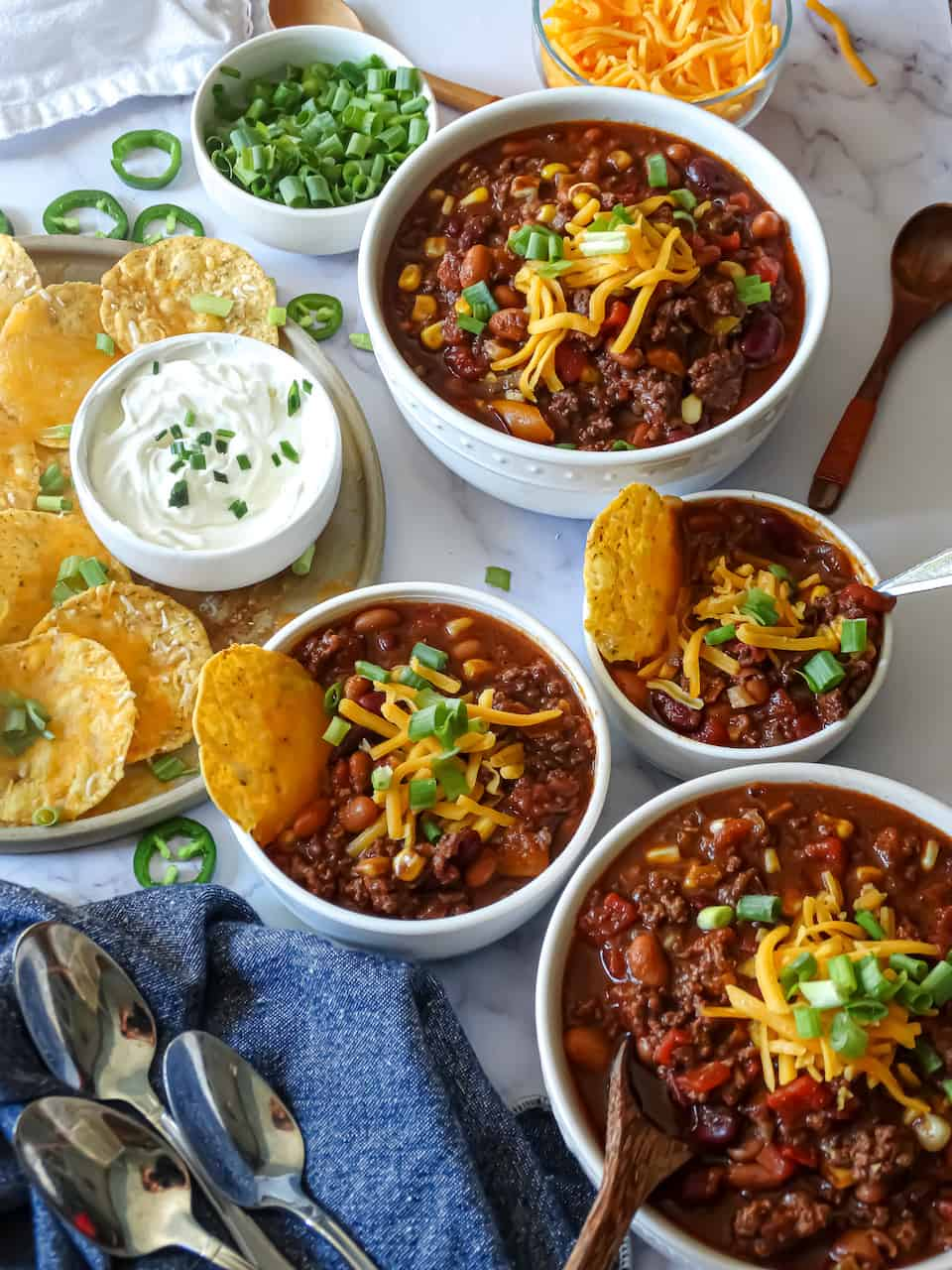 easy instant pot chili recipe in family size bowls with tortilla chips, green onions, cheddar cheese, and jalapeños against a white background