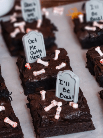 halloween graveyard brownies with tombstones and bones on parchment paper