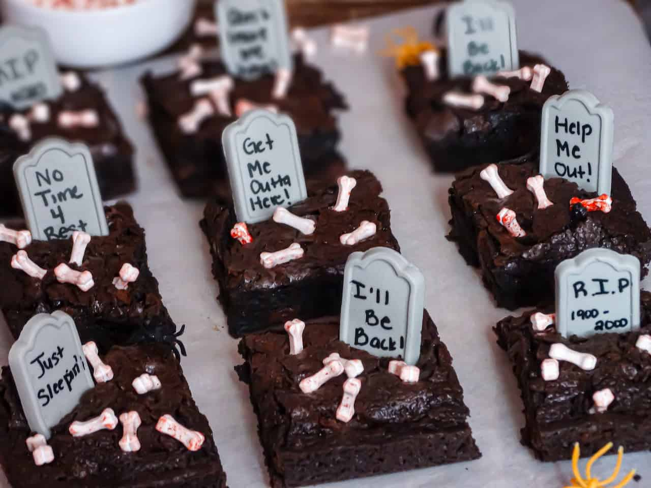 halloween brownies cut into squares with graveyard stones, bones, and spiders