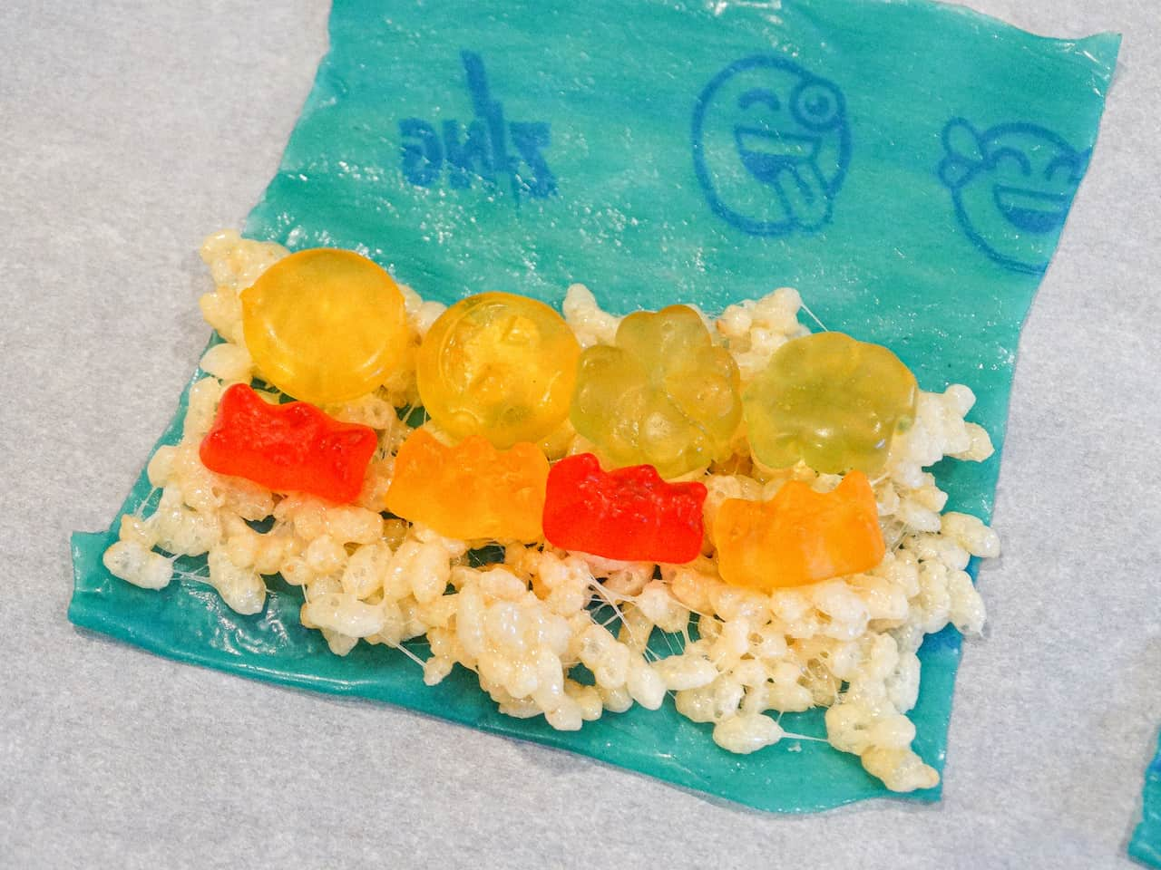 a fruit roll up topped with rice mixture and gummy candy on a piece of parchment paper