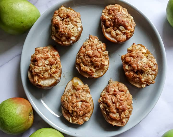 baked pears with apple crisp topping on a grey plate
