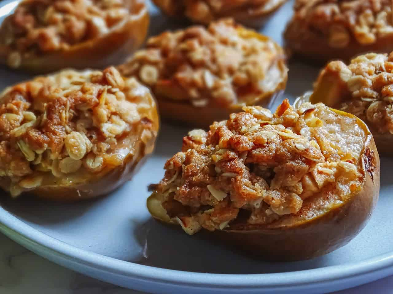 baked pears filled with apple crisp topping on a grey plate
