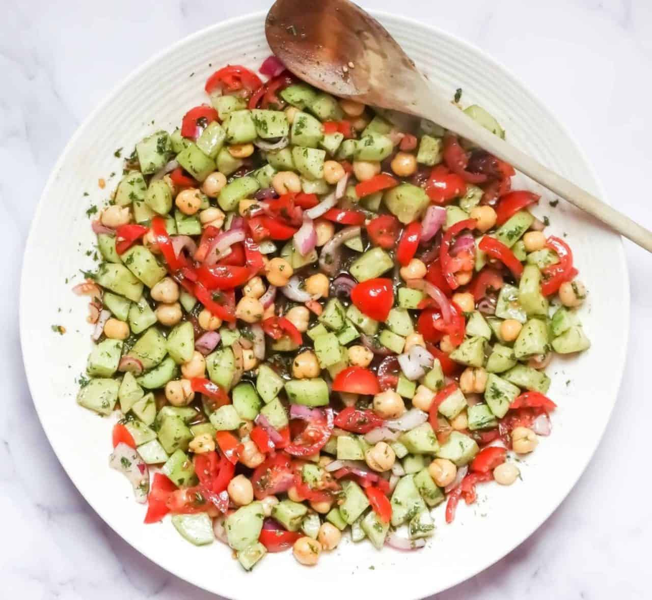 chickpeas, onions, tomatoes, and cucumber on a white plate mixed with balsamic dressing