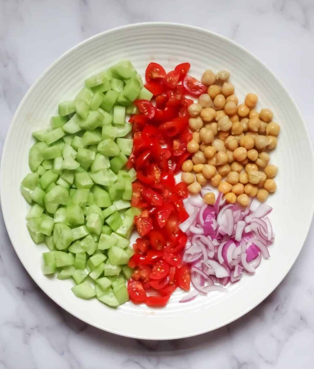 chickpeas, onions, tomatoes, and cucumber on a white plate