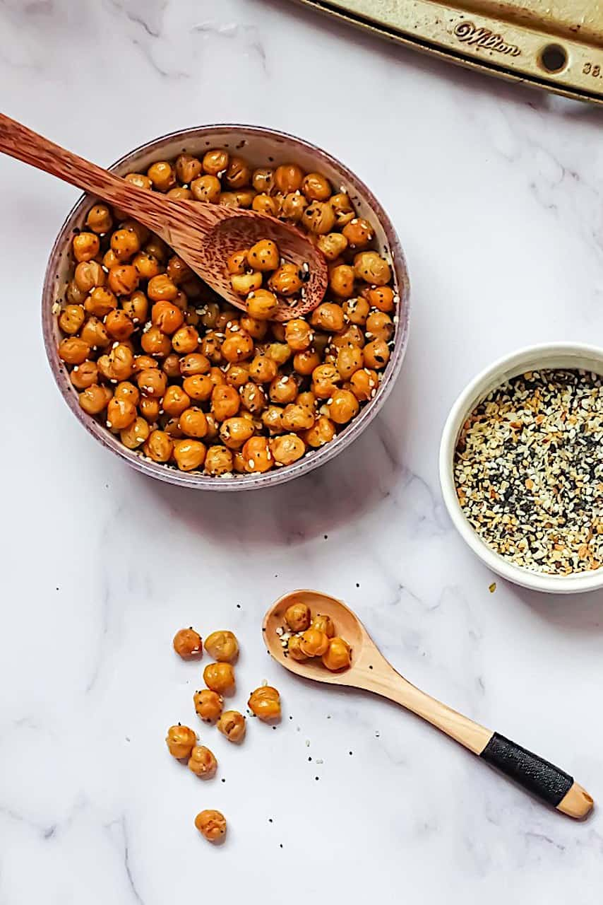 crispy roasted chickpeas in a white bowl with a white background and surrounded by everything bagel seasoning