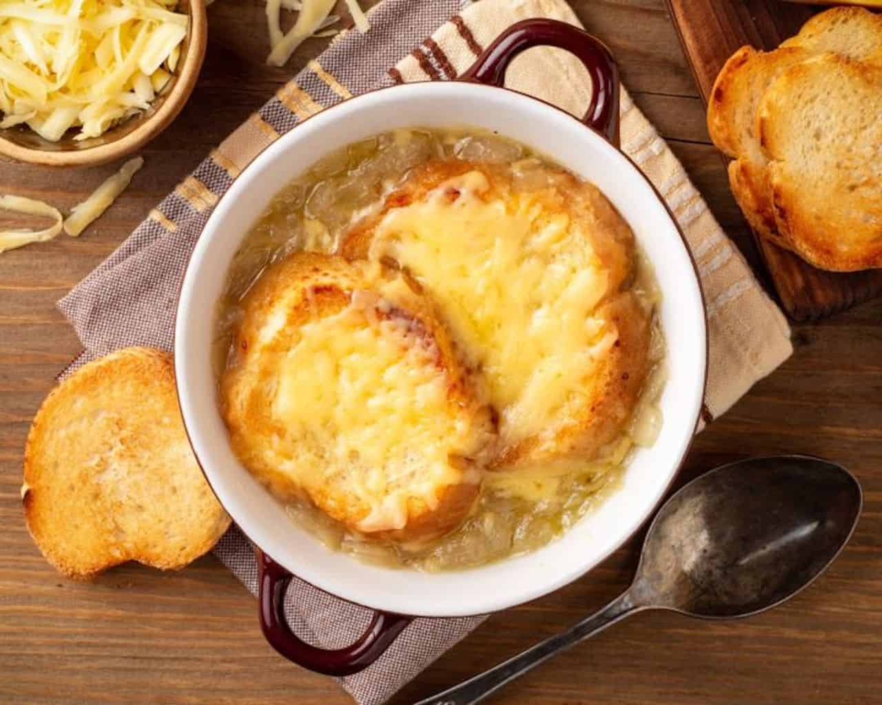 Traditional French Onion soup topped with melted cheese and bread in a white crock.