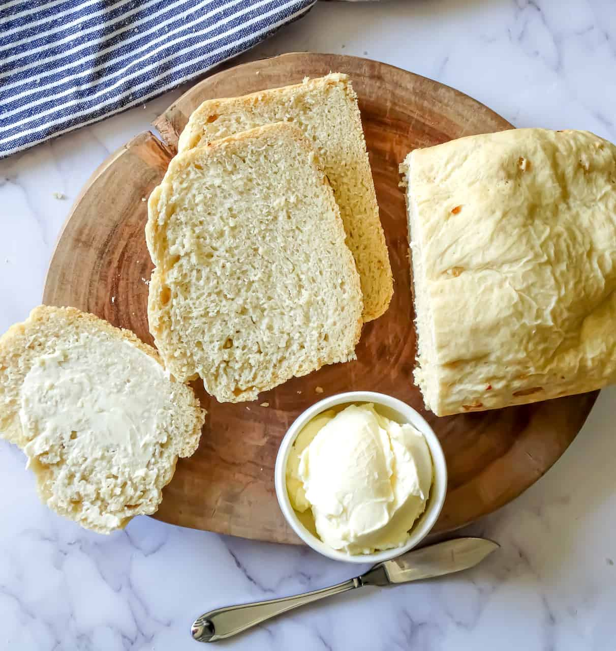 homemade bread machine garlic bread cut into slices and served with butter on a wooden background