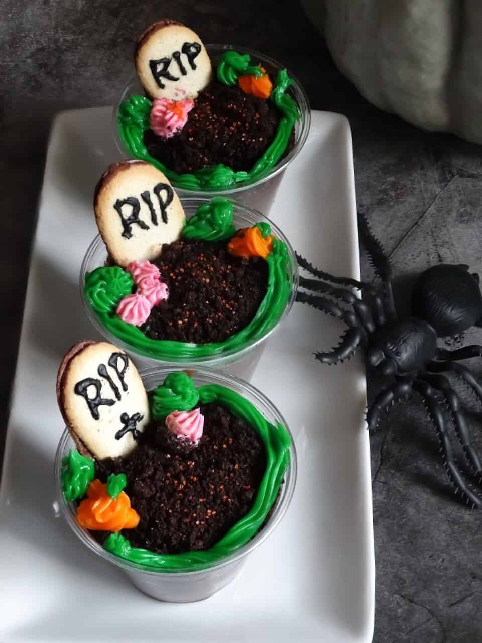 Halloween graveyard chocolate pudding cups on a white serving plate and a gray background