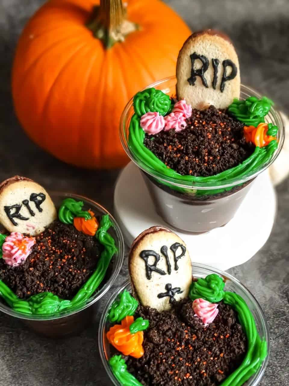 Halloween graveyard treats: chocolate pudding cups decorated with cookies and icing