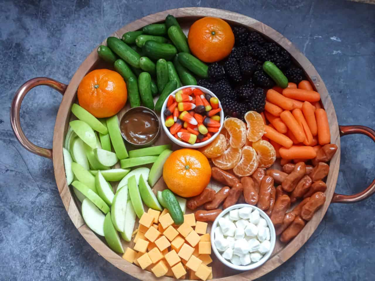 healthy Halloween charcuterie board with orange, black, green, and yellow foods