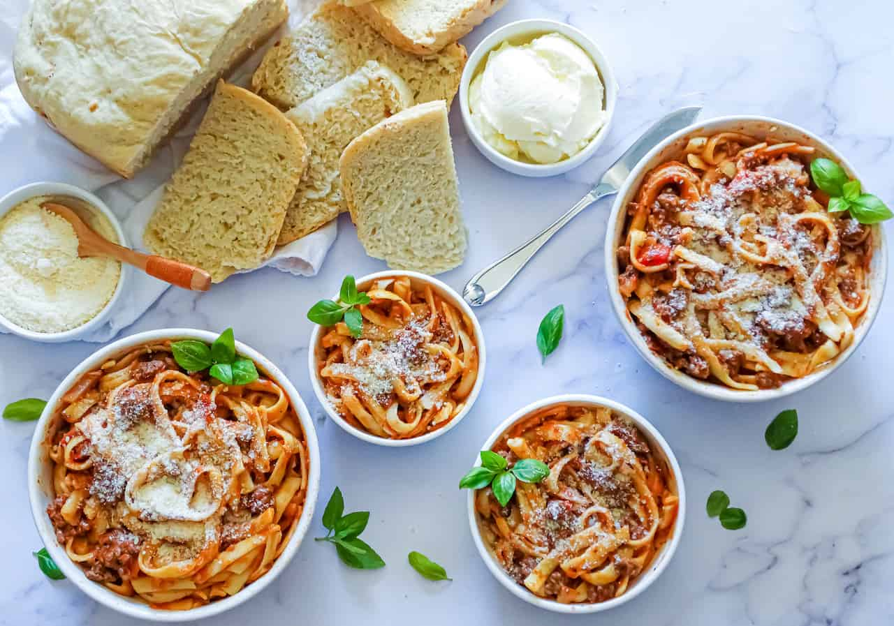 INSTANT Pot spaghetti in 4 bowls topped with parmesan cheese and basil leaves on a white background with garlic bread