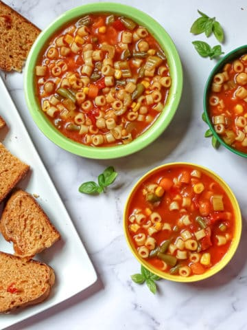 instant pot vegetable soup in kids and adult bowls served with tomato basil bread on a white background