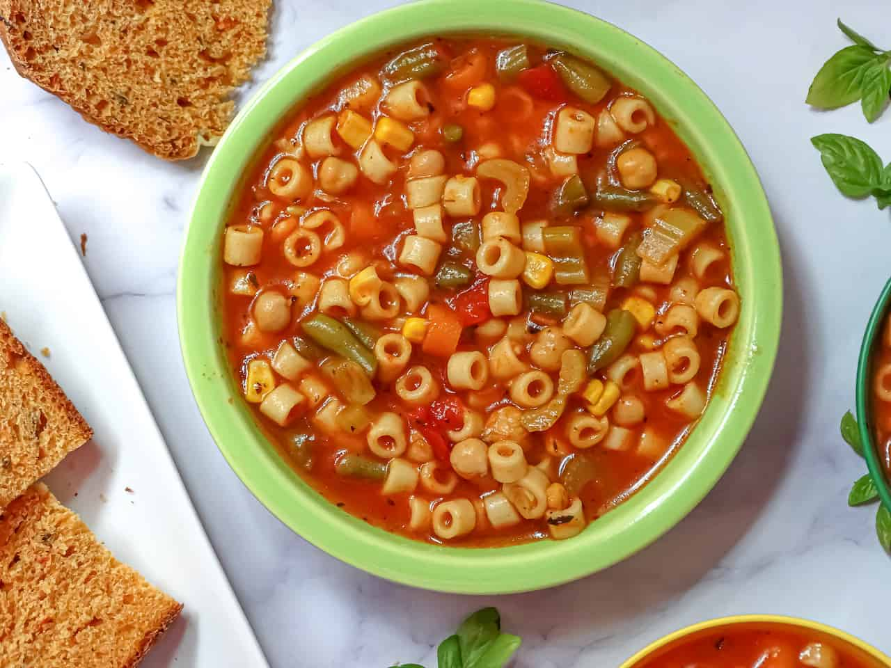 instant pot vegetable soup in a green adult bowl served with tomato  basil bread on a white background