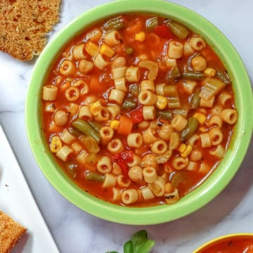 instant pot vegetable soup in a green bowl with tomato basil bread