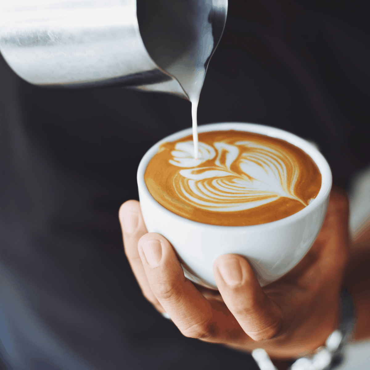 milk being poured into a coffee cup