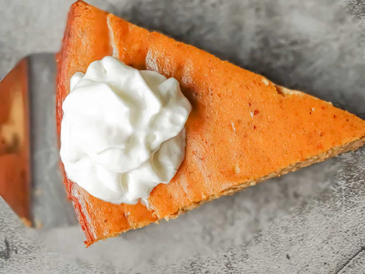overhead shot of a slice of pumpkin spice cheesecake with nutmeg crust and whipped cream