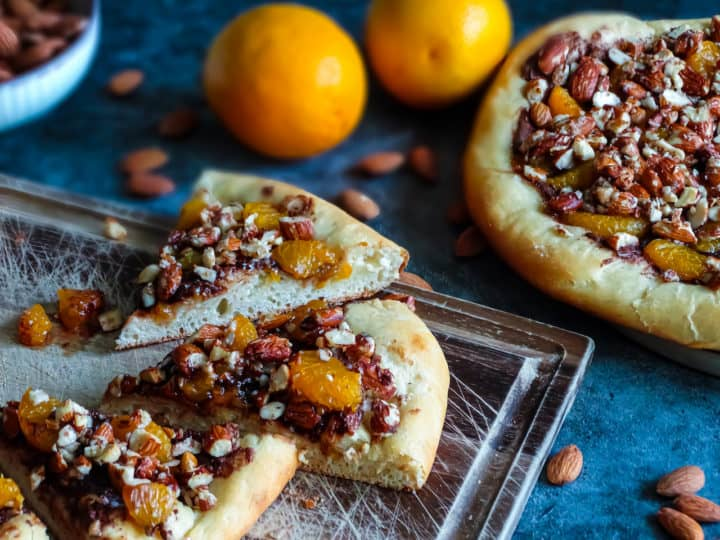 chocolate orange hazelnut fruit pizza cut into slices on a cutting board with oranges and almonds in the background