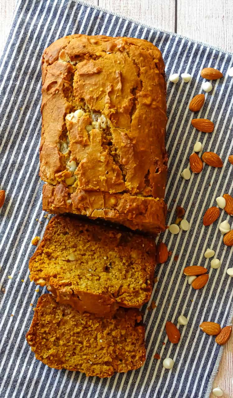 pumpkin chocolate chip bread cut into slices on a blue striped towel and surrounded by almonds and white chocolate chips
