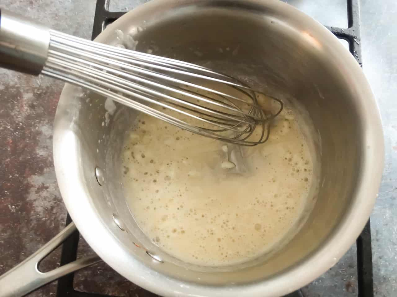 the roux for white cream sauce with milk in a pot being stirred with a whisk