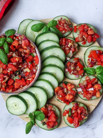 homemade bruschetta on cucumber slices arranged on a circular cutting board and topped with basil leaves