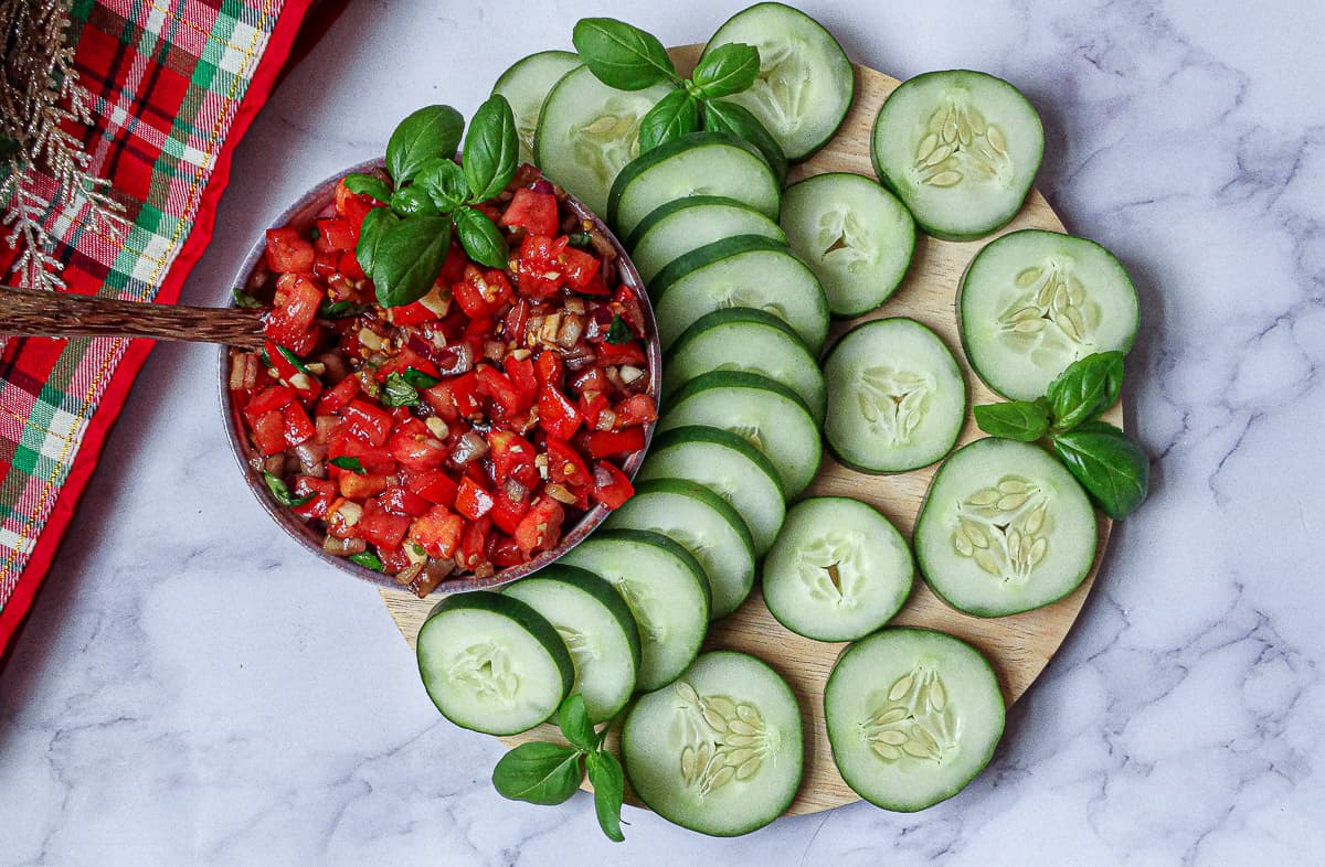 cucumber slices arranged on a circular cutting board and homemade bruschetta in a bowl