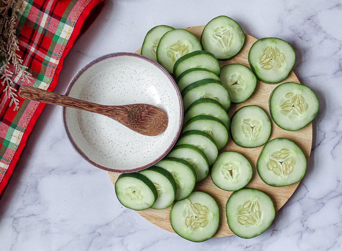 cucumber slices arranged on a circular cutting board in preparation for becoming a Christmas appetizer