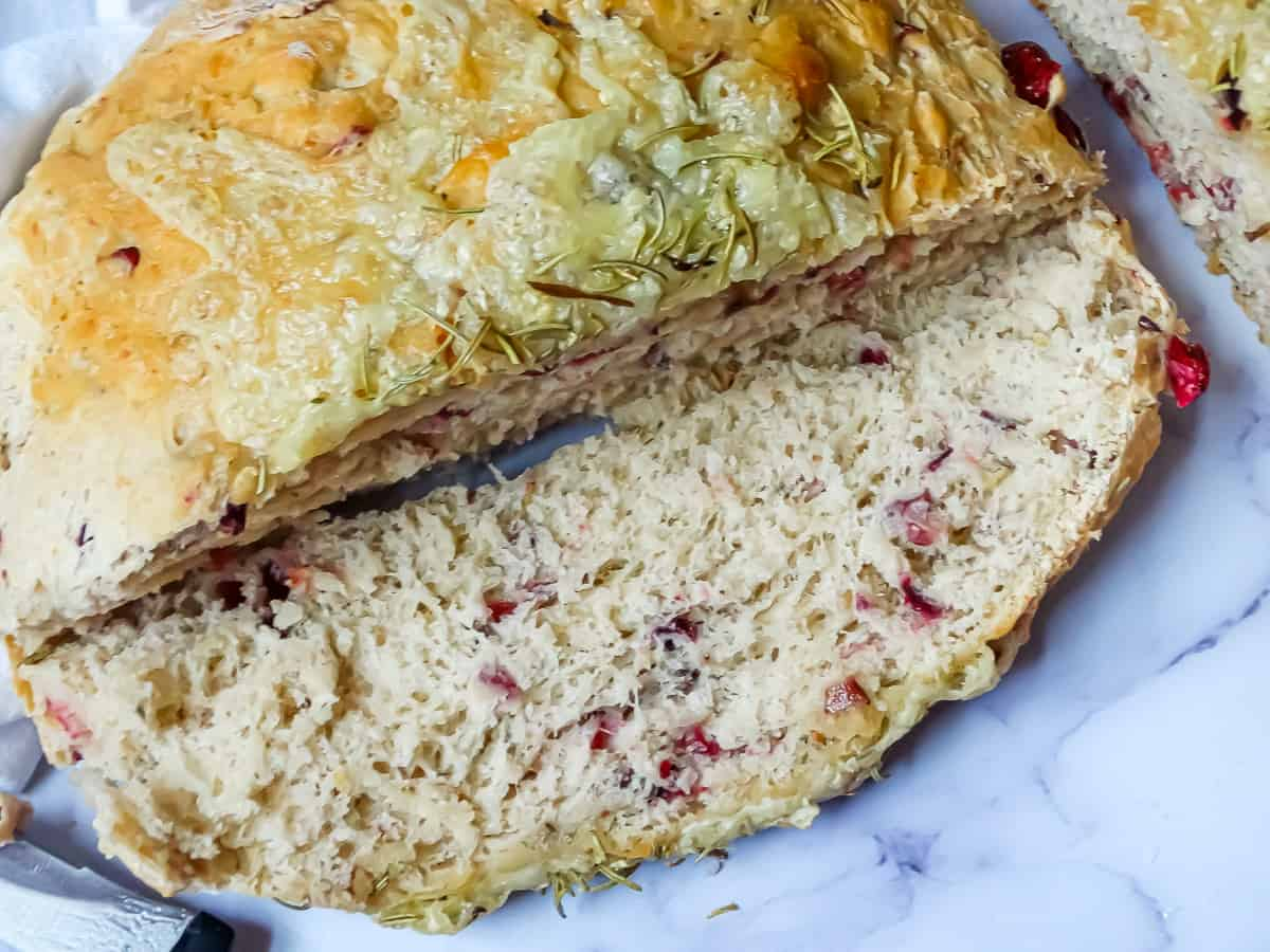 one slice of baked brie cranberry bread on a white cutting board