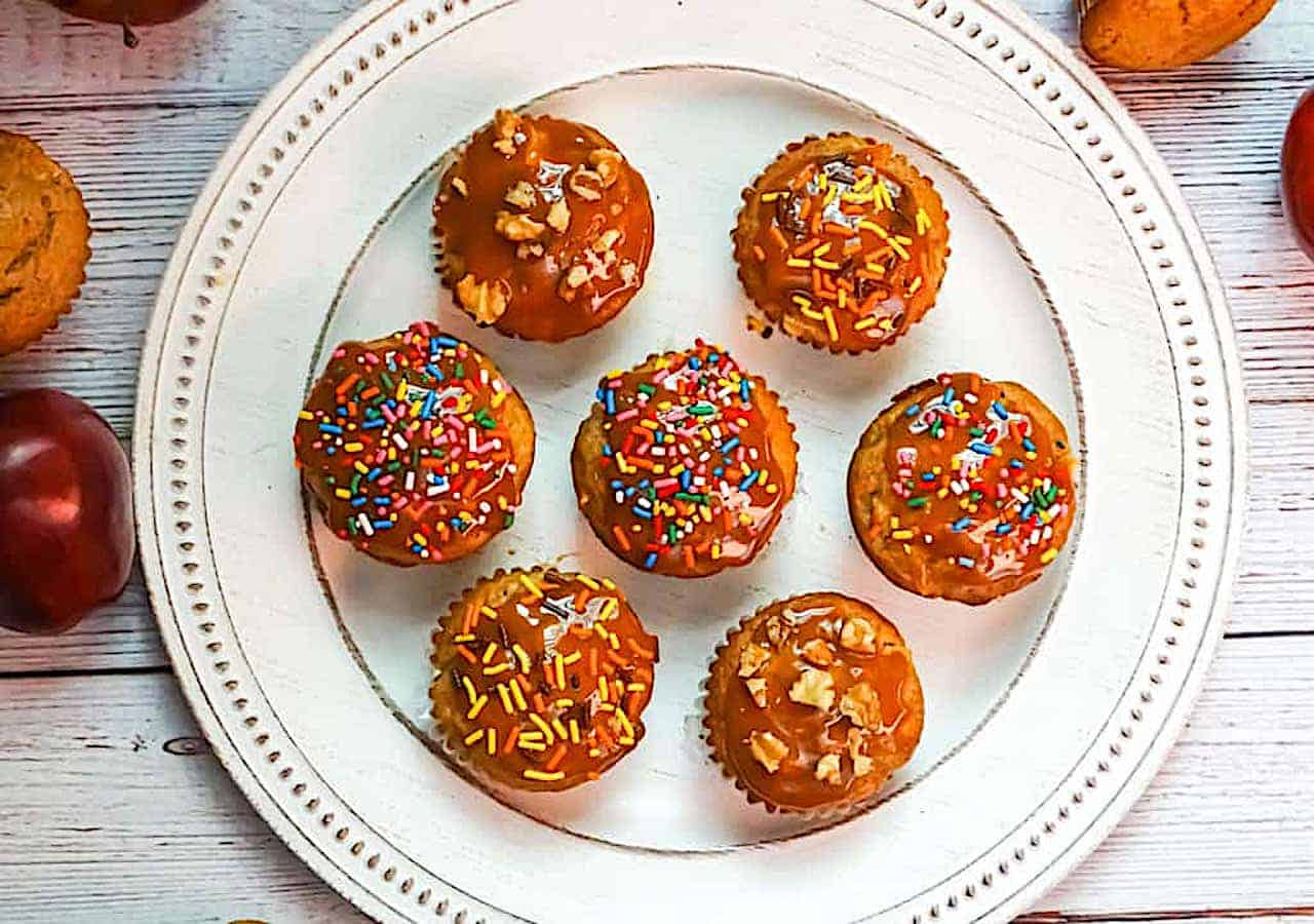 caramel apple muffins with caramel, sprinkles and nut topping on a white plate
